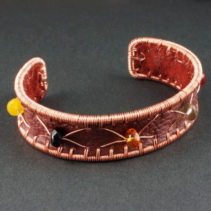 Copper cuff bracelet with leather and glass beads.